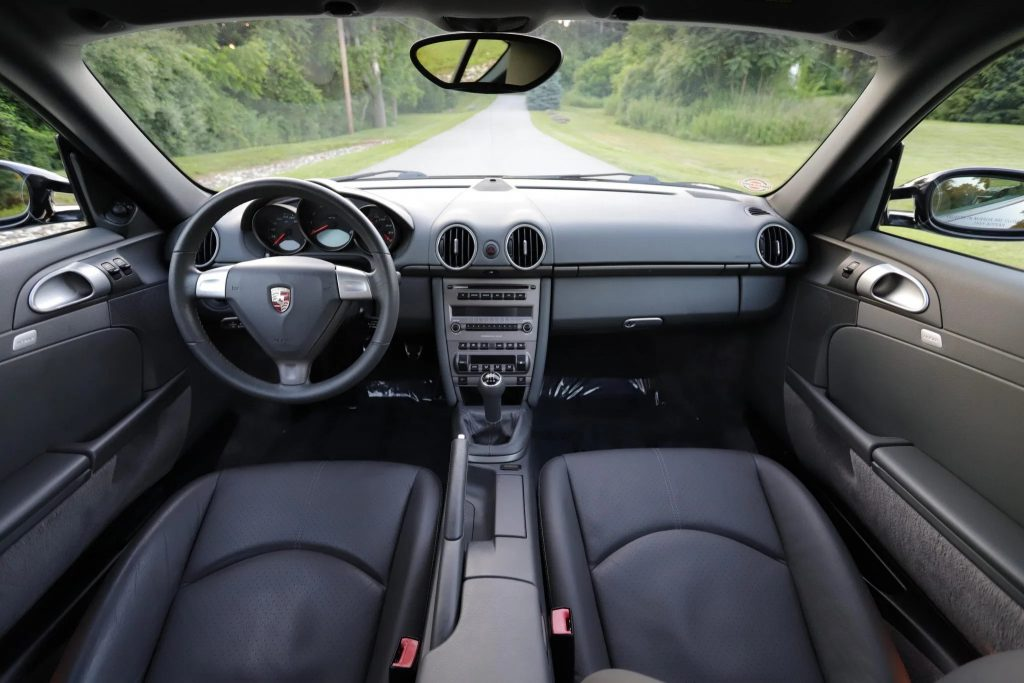 The gray-leather-upholstered seats and dashboard of a 2007 Porsche Cayman 5-Speed