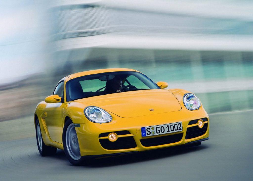 A yellow 2007 Porsche Cayman slides around a corner