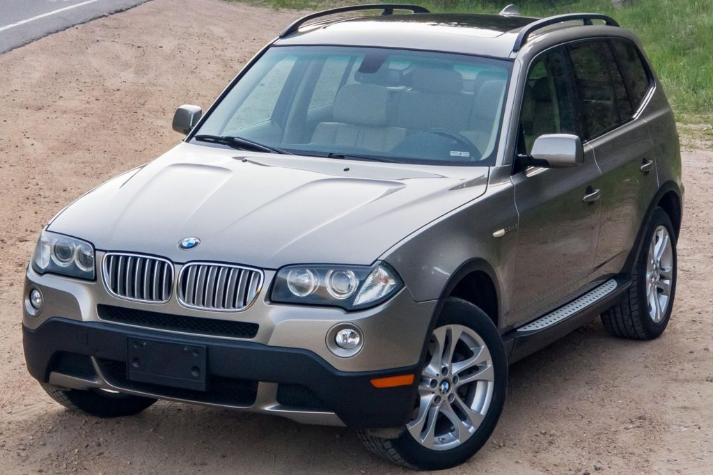 A tan 2008 BMW X3 3.0si parked by the side of the road