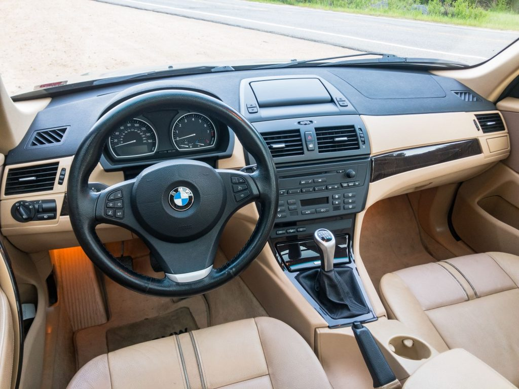 The tan-leather-upholstered front seats and ash-wood-trimmed tan-and-black dashboard of a 2008 BMW X3 3.0si
