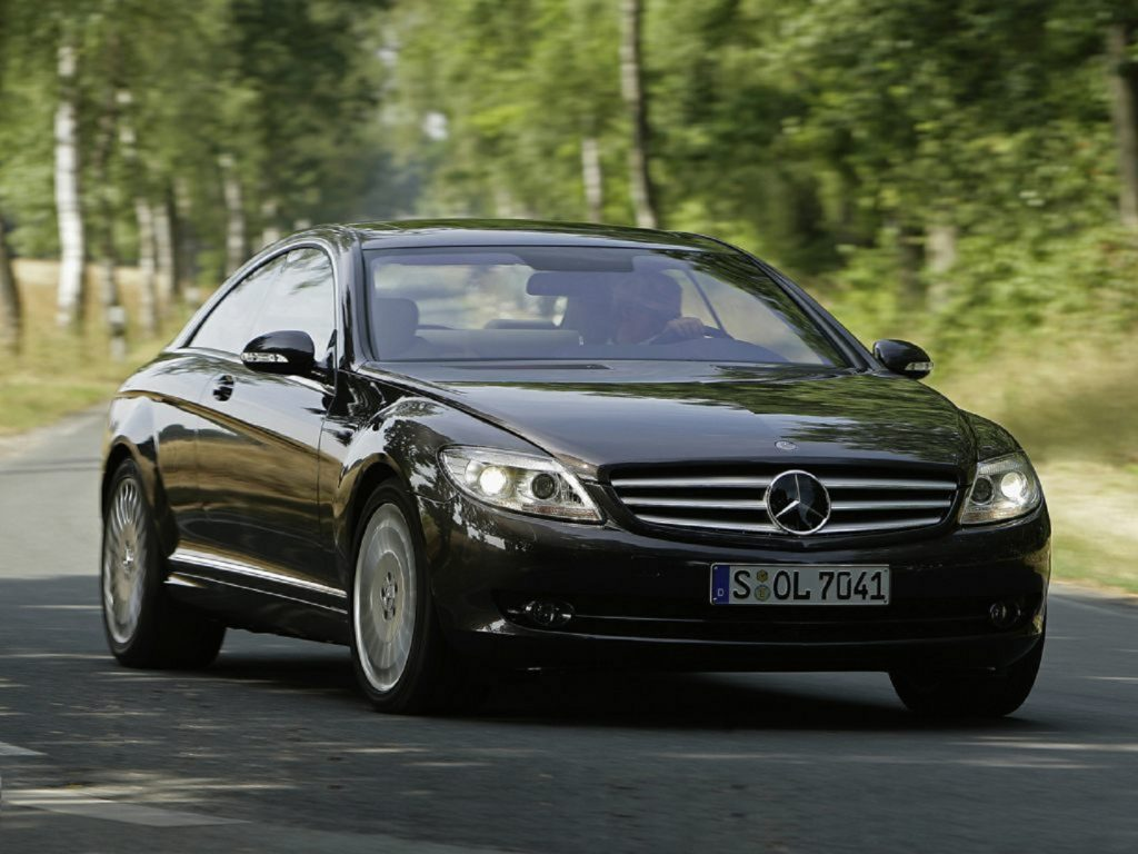 A black 2010 Mercedes-Benz CL550 4Matic driving down a tree-lined road