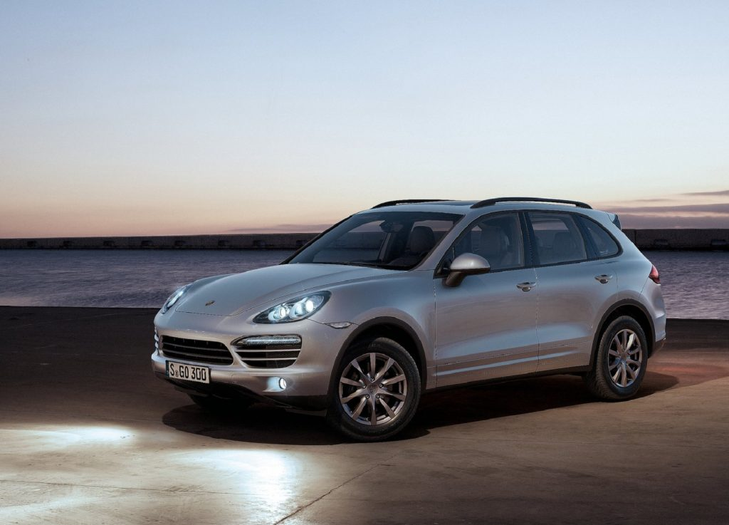A silver '958' 2011 Porsche Cayenne with its lights on by the ocean