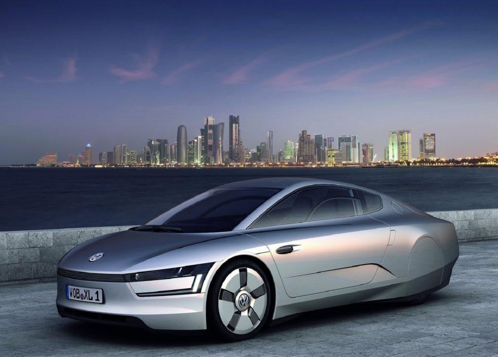 The silver 2011 Volkswagen XL1 Concept overlooking an oceanside city