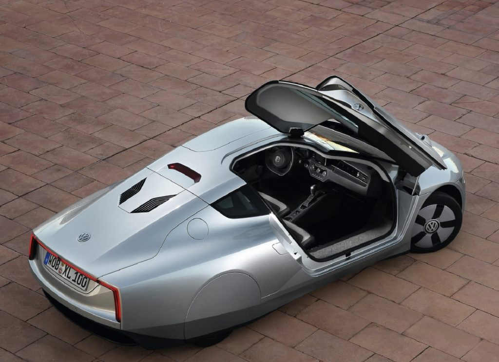 An overhead rear 3/4 view of a silver 2014 Volkswagen XL1 with its passenger-side door open