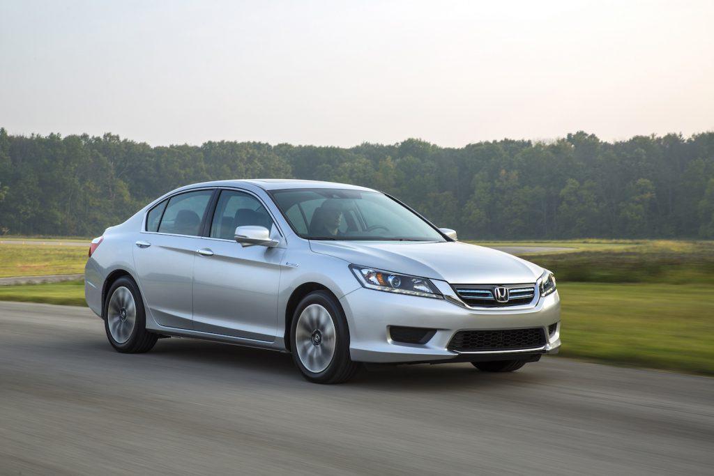 A silver 2015 Honda Accord Hybrid EX-L driving, the 2015 Honda Accord Hybrid is the best used hybrid under $20,000