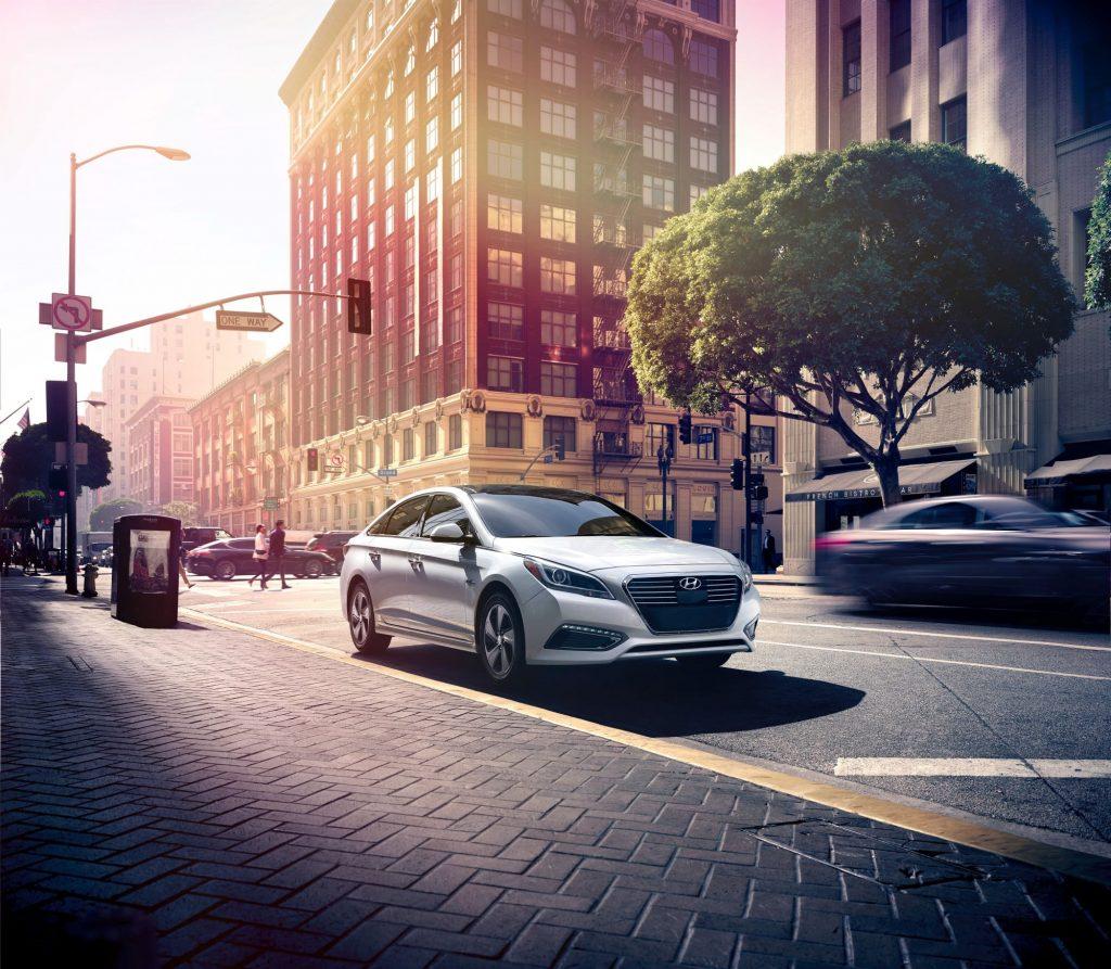 A silver gray 2016 Hyundai Sonata Hybrid model parked next to a cobblestone walking path