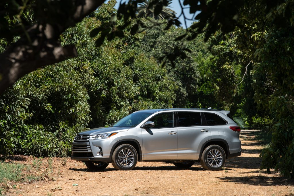 A silver 2017 Toyota Highlander parked amongst trees, the 2017 Toyota Highlander is the best CPO three-row SUV under $30,000