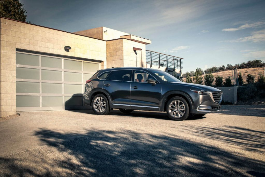 A dark grey 2018 Mazda CX-9 parked in a driveway, the 2018 Mazda CX-9 is one of the best CPO three-row SUVs under $30,000