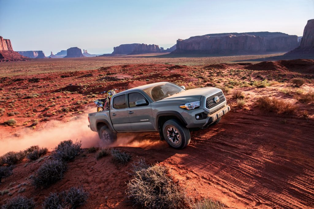 A dusty 2018 Toyota Tacoma flies up a dirt trail