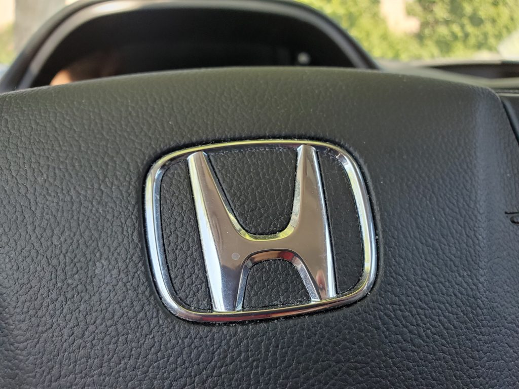 Close-up of a silver Honda logo on a black CR-V steering wheel