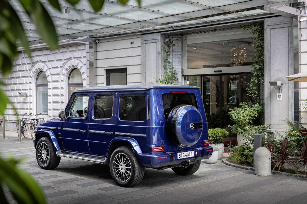 A blue 2019 Mercedes-Benz G-Class luxury SUV parked in front of a white building in Germany