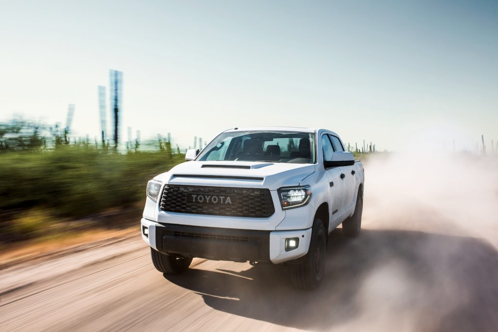 A white 2019 Toyota Tundra driving down a dirt road with dust surrounding it, the 2019 Toyota Tundra is one of the most reliable used Toyota Tundra model years