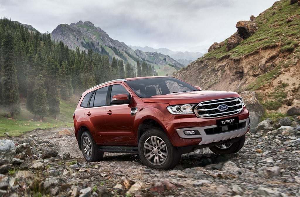 A red 2019 Ford Everest driving up a rocky trail
