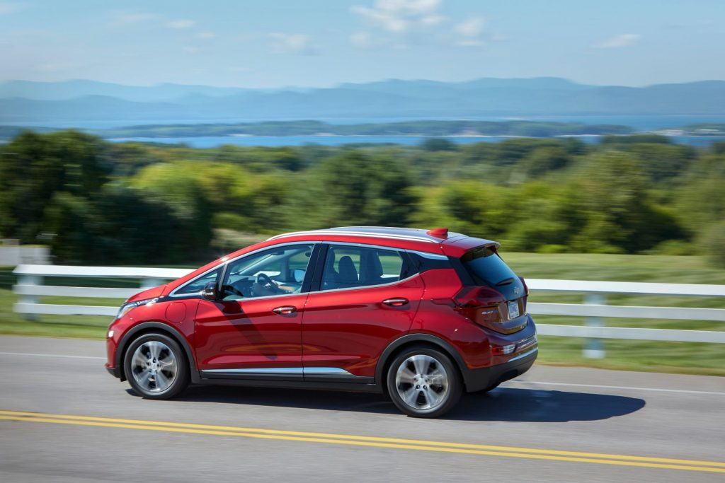 A red 2020 Chevrolet Bolt EV model driving on a highway past a white fence and grass fields