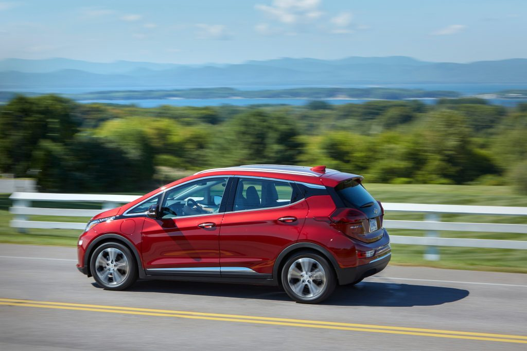 Red 2020 Chevy Bolt EV drives on waterfront road.