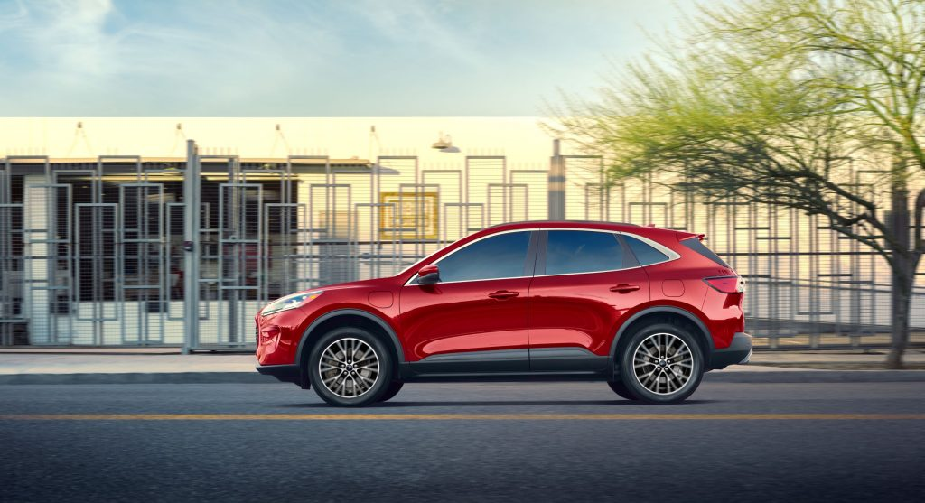 The side view of a red 2020 Ford Escape Plug-In Hybrid on a city street