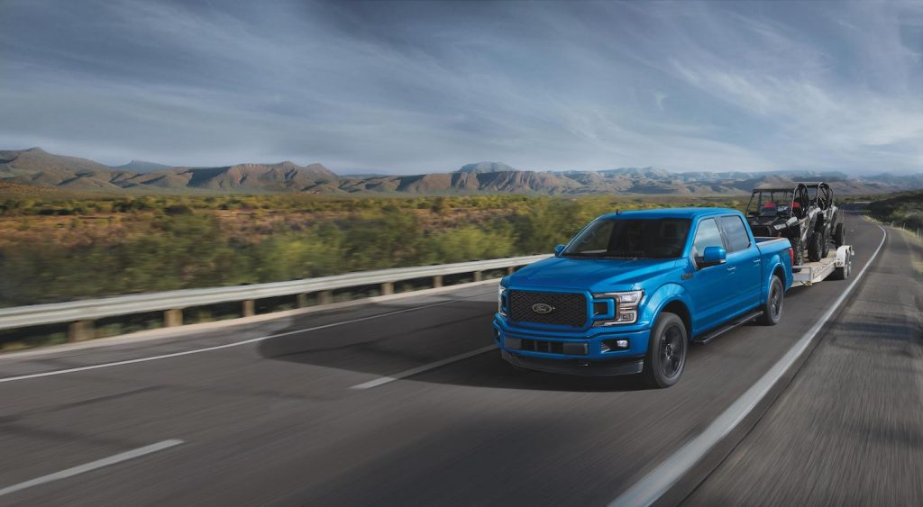 A blue 2020 F-150 XLT driving, the Ford F-150 is a used truck