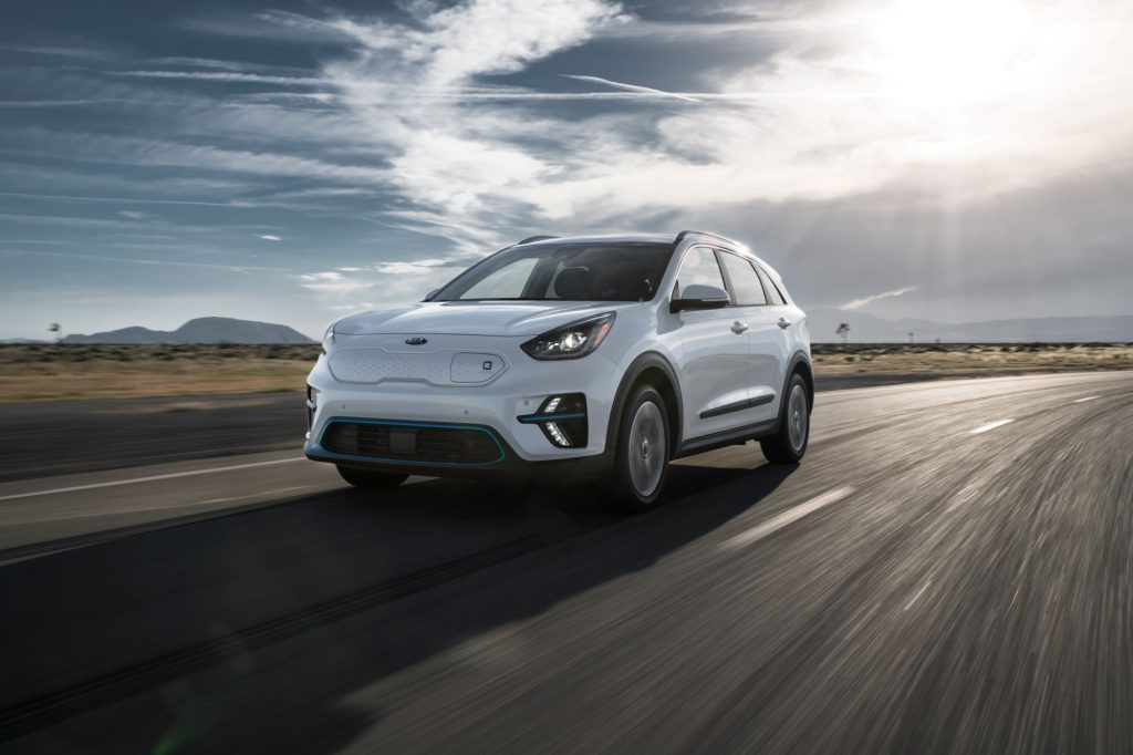 A white 2020 Kia Niro EV driving on a highway on a cloudy day in a plain with one small hill.