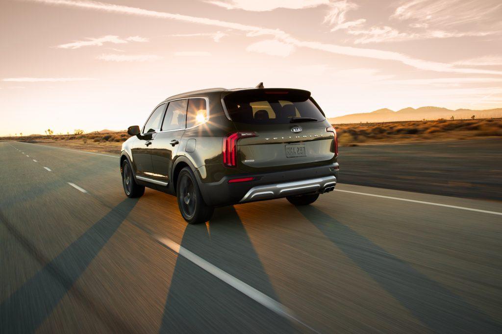 A dark-green 2020 Kia Telluride midsize SUV traveling on a highway through a desert