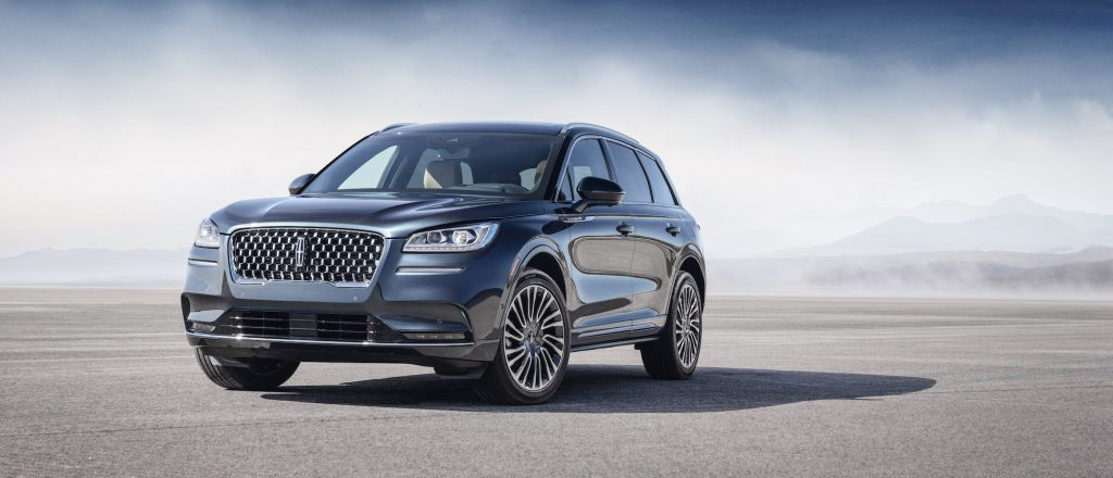 A bluish-gray 2020 Lincoln Corsair luxury compact SUV parked on asphalt in front of mist and mountains