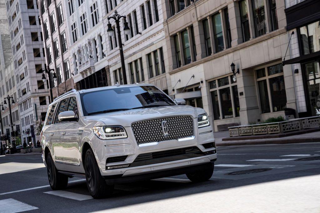 A white 2020 Lincoln Navigator luxury SUV model driving through an urban city environment