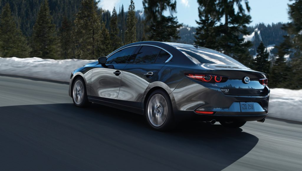 A dark-gray metallic 2020 Mazda3 sedan traveling on a mountain road past snow and pine trees on a sunny day