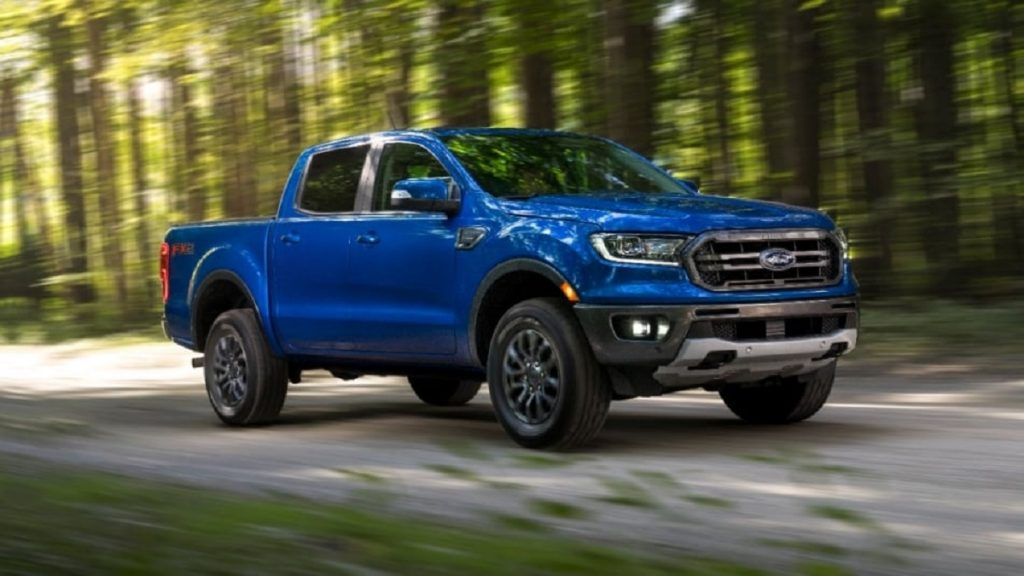 A blue 2020 Ford Ranger drives down a wooded road.