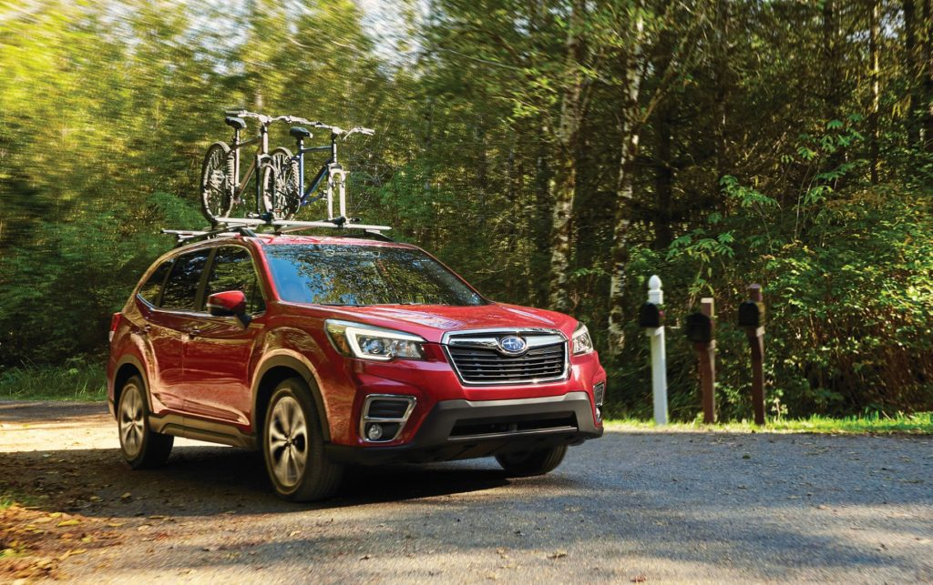A red 2020 Subaru Forester in a wooded area parked on a dirt road with bicycles on the top rack.
