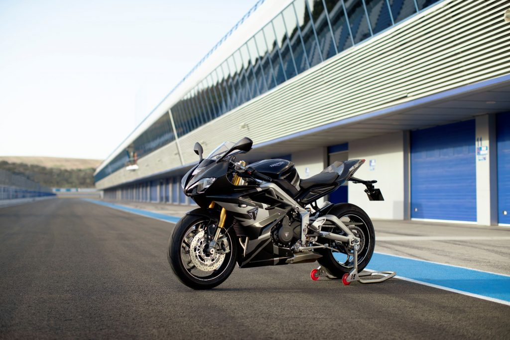The black-and-silver 2020 Triumph Daytona Moto2 765 Limited Edition on a rear-wheel stand on a racetrack