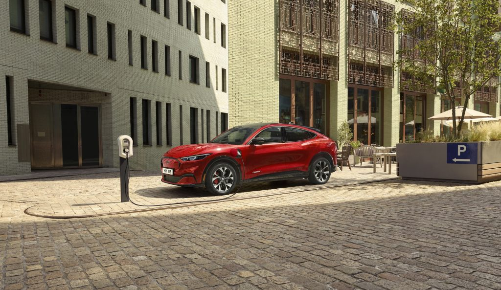 A red Mach-E sits on a street corner plugged into a charger in the sun