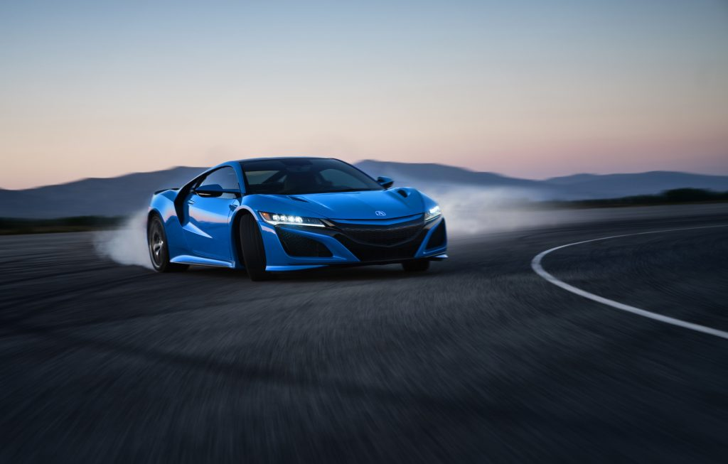 A bright-blue 2021 Acura NSX sports car turns a corner on a track with mountains in the distance