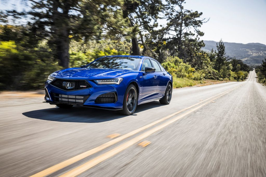 A blue 2021 Acura TLX Type S model driving down a forest highway