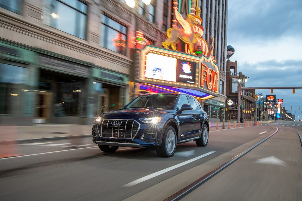 A dark-blue metallic 2021 Audi Q5 traveling on a city street past a theater marquee