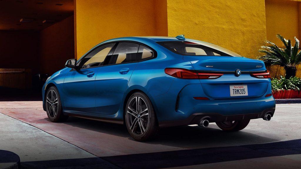 A blue BMW 2 series sedan against a yellow wall