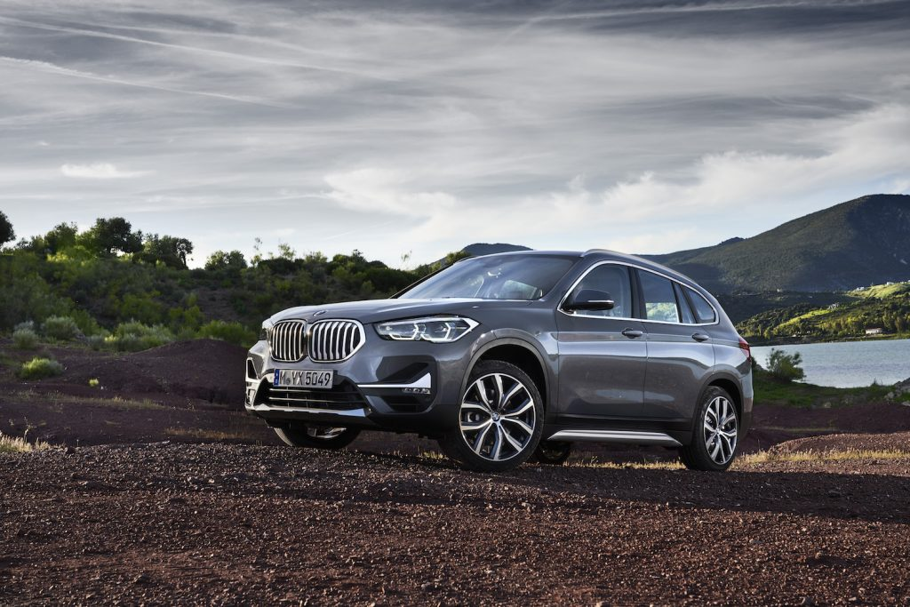 A grey 2021 BMW X1 driving up a hill, the 2021 BMW X1 is the cheapest new BMW SUV