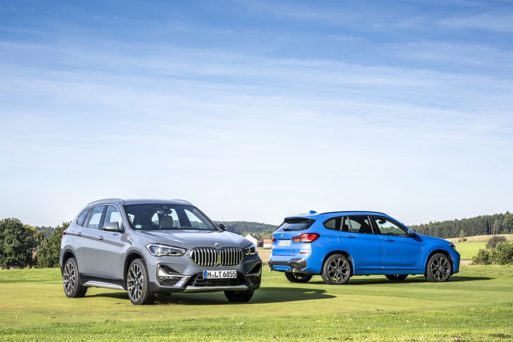 Two 2021 BMW X1 luxury compact SUVs parked on a large green lawn in front of rolling hills and trees