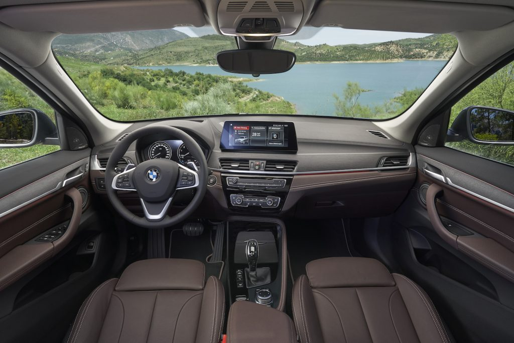 The interior of the 2021 BMW X1, featuring leather seating and a touchscreen display