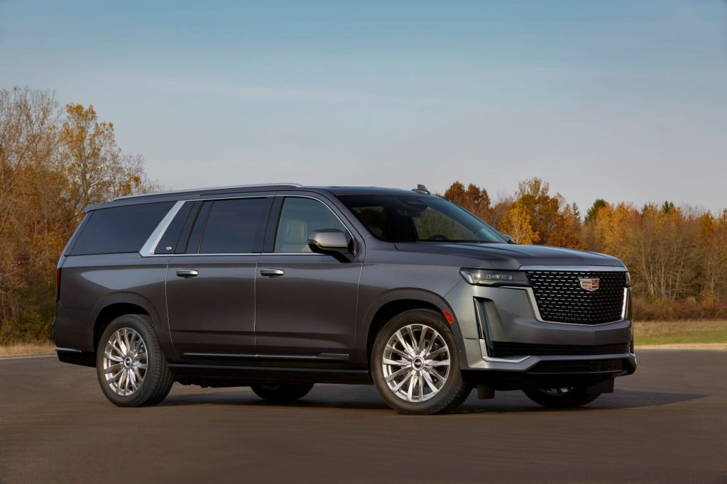 The 2021 Cadillac Escalade full-size SUV with gray metallic paint parked on an asphalt lot near a forest of trees