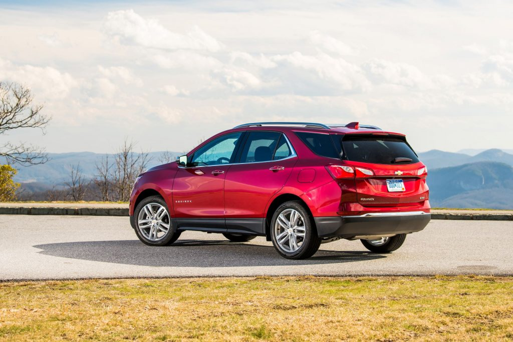A red 2021 Chevrolet Equinox parked on a concrete drive surrounded by grass with trees and mountains in the background.