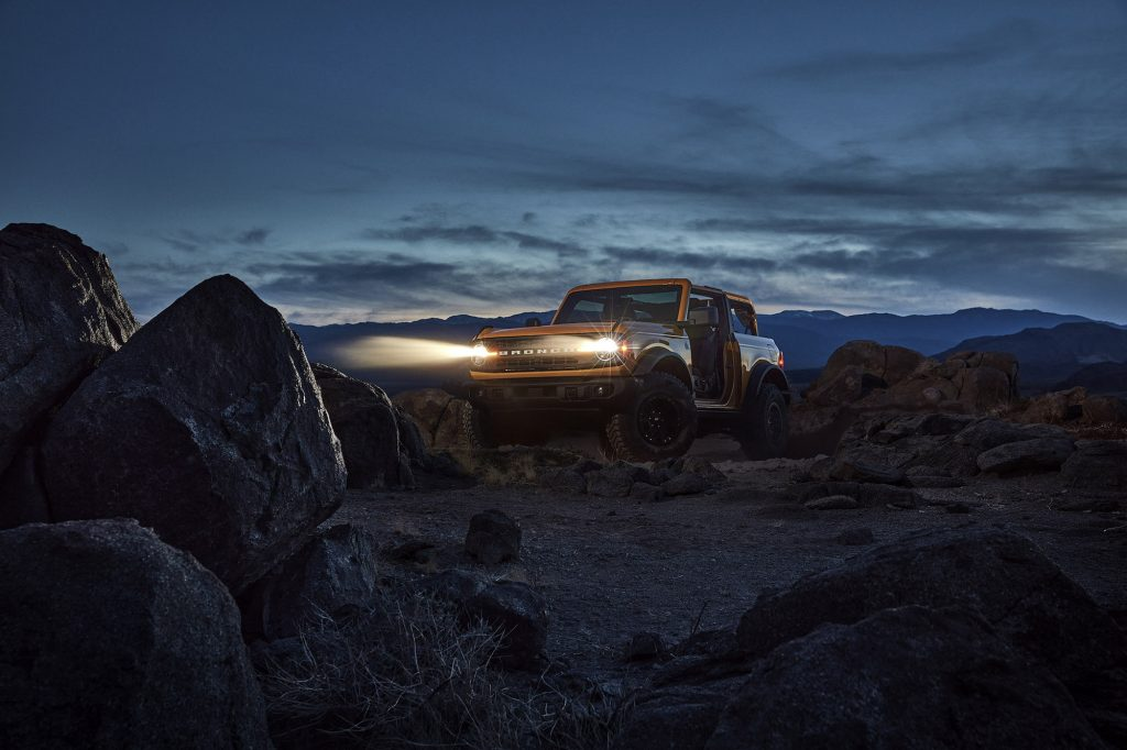 A yellow 2021 Ford Bronco with its headlights on as it sits on rocks in front of mountains at night