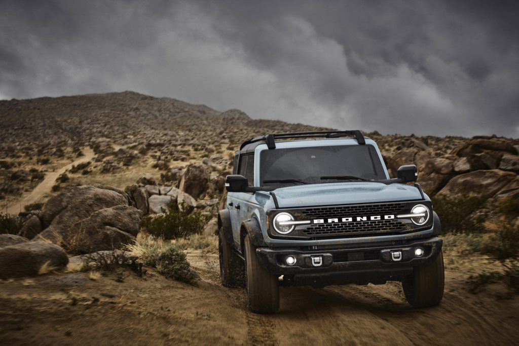 A 2021 Ford Bronco climbing a trail, the Bronco is a new car being sold over list price