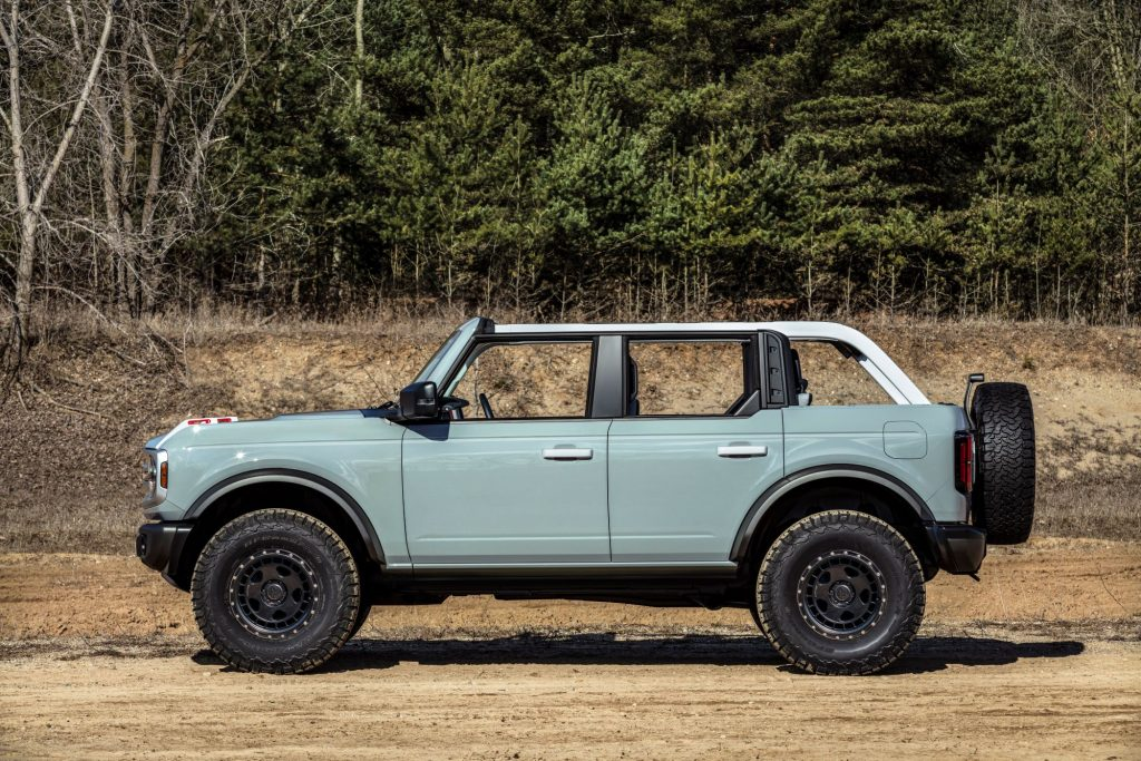 A four-door 2021 Ford Bronco model parked on a dirt plain near a forest