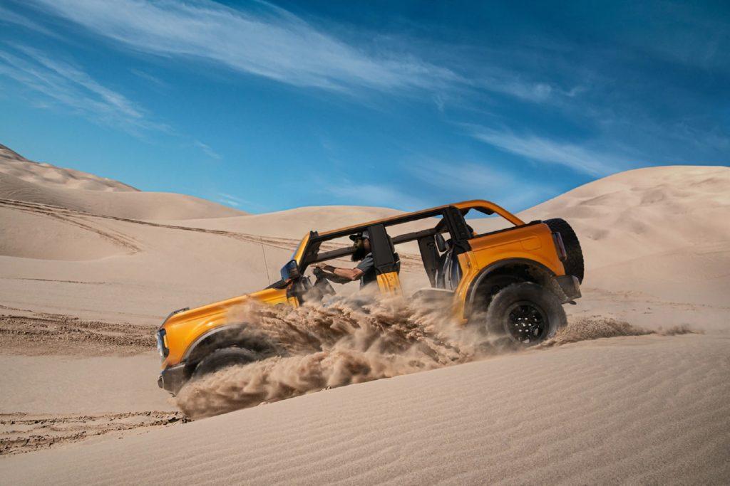 An orange 2021 Ford Bronco Wildtrak 4-door with no doors or roof drives down a desert dune