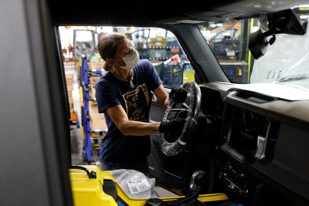 A Ford employee assembles a steering wheel on a 2021 Ford Bronco