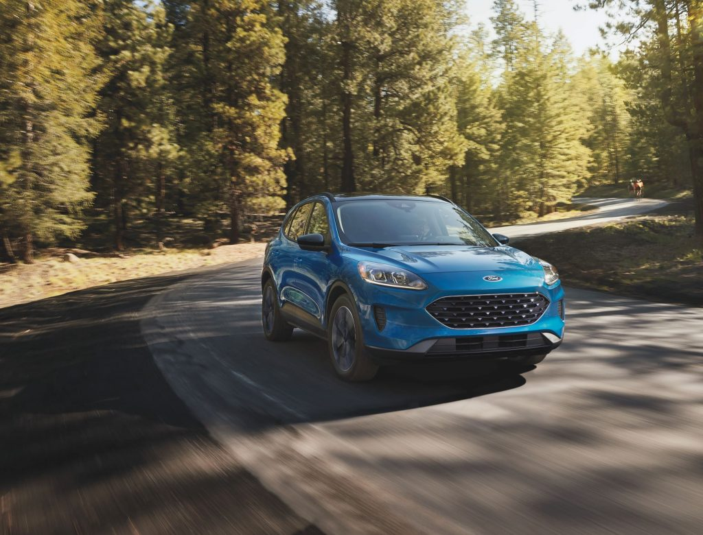 A teal 2021 Ford Escape Driving on a highway in a very wooded area.