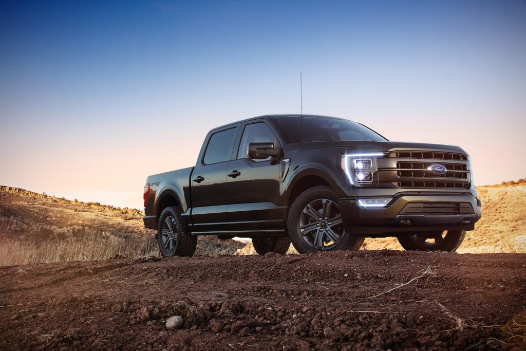 A black 2021 Ford F-150 parked on a dirt hill at dusk