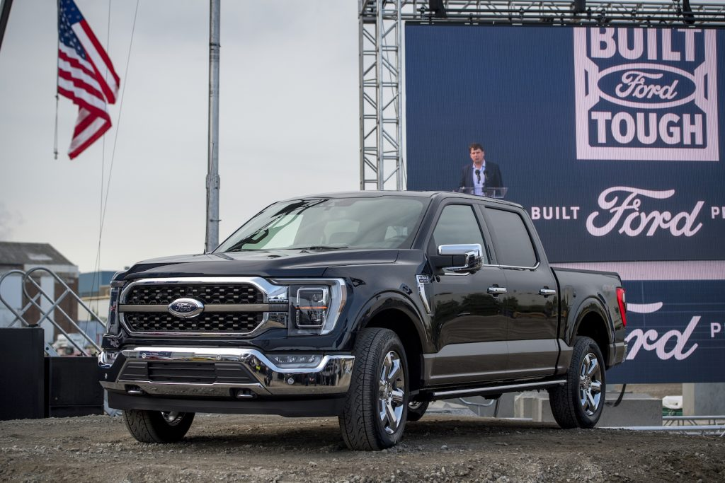 A Black 2021 Ford F-150 with an American flag and a billboard behind it, the Ford F-150 is among the best trucks of 2021