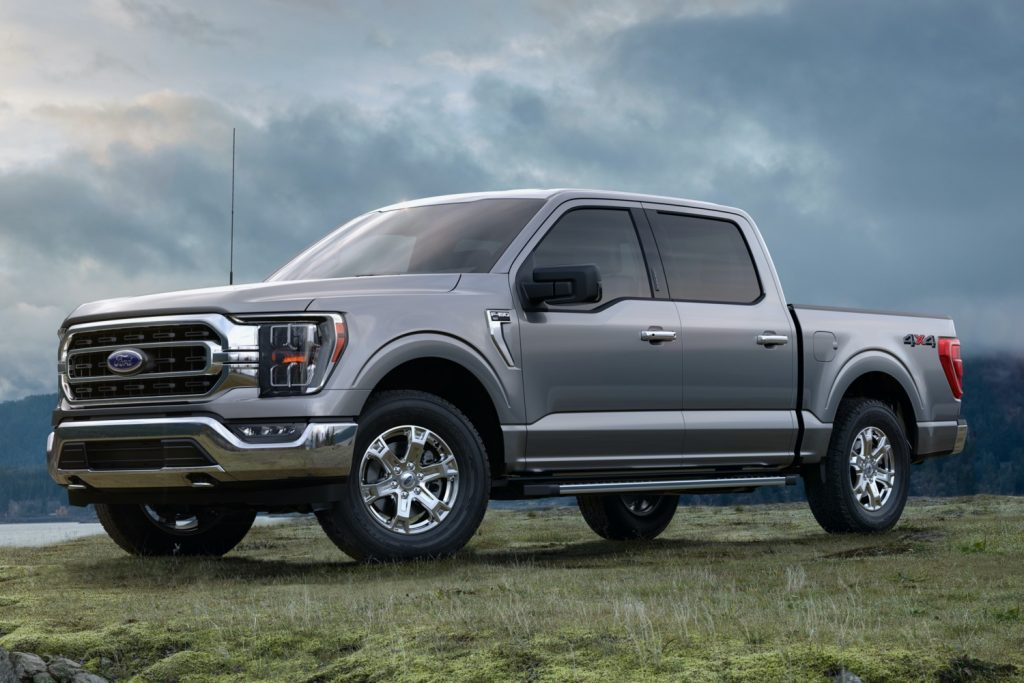 A grey 2021 Ford F-150 parked in grass on a cloudy day