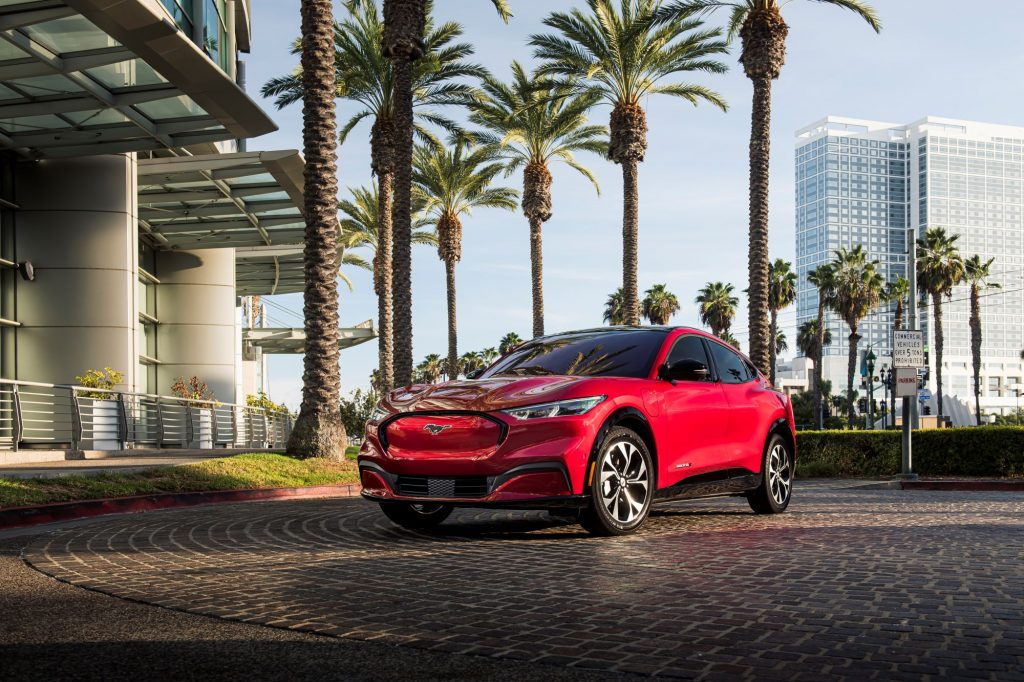 A red 2021 Ford Mustang Mach-E sits on a brick driveway surrounded by palm trees and modern buildings.