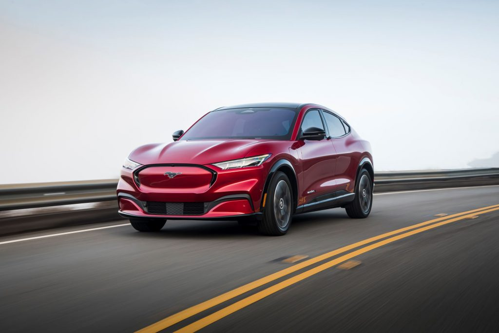 A red 2021 Ford Mustang Mach-E driving on a highway